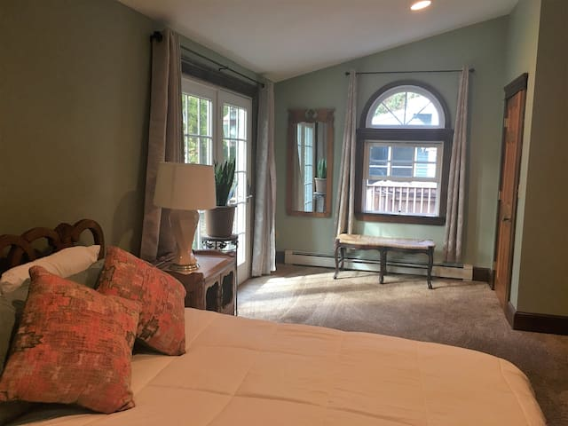 Large master bedroom with arched windows, vaulted ceilings, recessed lighting.