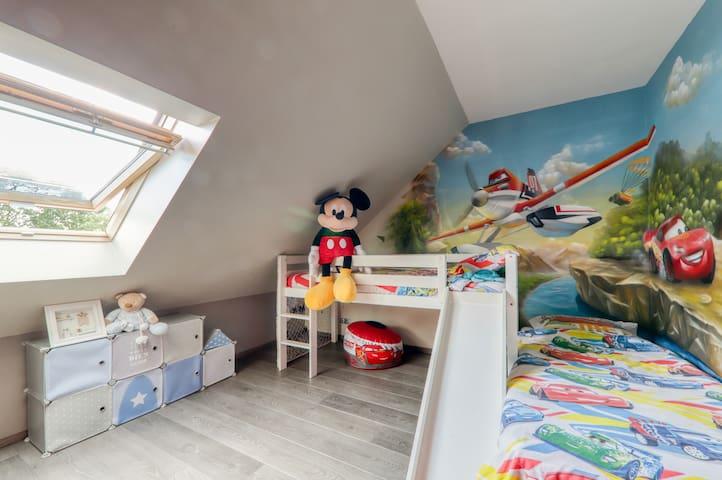 Chambre 3_chambre d'enfants  : décoration murale thème Disney Cars avec un lit simple mezzanine et un lit simple. Un grand placard, une commode, un bureau et sa chaise. Vue 1
