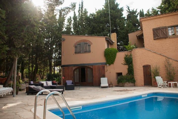 Casa assolellada amb piscina i espais d'esbarjo.