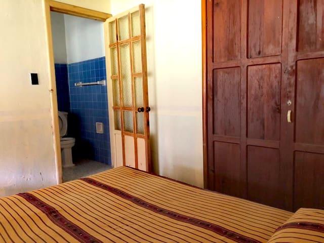 Habitación con cama matrimonial y baño incluido.