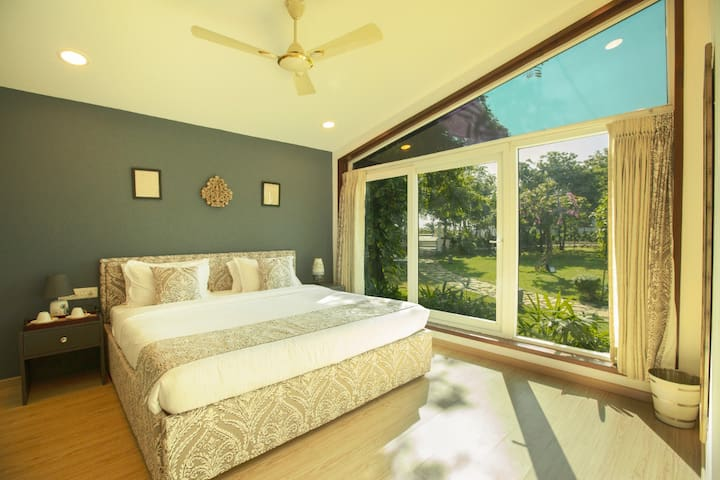 Ultra modern Bedroom 1 with garden view. Chic wooden floors and tastefully furnished. Wake up to sunrise or a dark room as you prefer.
