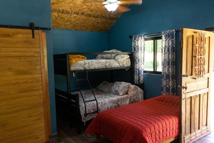 Cuenta con una litera (cama matrimonial abajo, individual arriba), una cama individual y un sofa cama