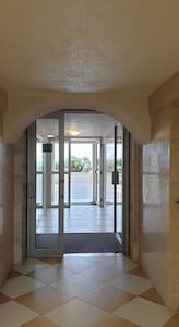 Entrée de la Résidence sans marche pour rejoindre l ascenseur. Photo prise de l intérieur.
