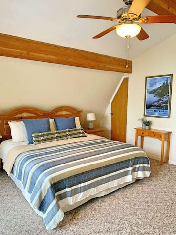 King size bed in second floor bedroom with balcony overlooking the lake and dedicated work space