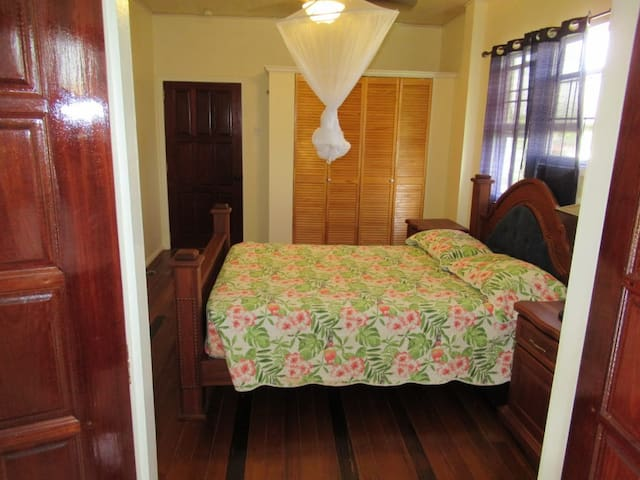 Queen bed with ceiling fan and air conditioning.
