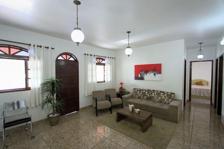 Ampla sala de estar com sofá, poltronas, mesa de centro e uma decoração aconchegante para relaxar depois de um dia de lazer. Wi-Fi 5g, banda larga de alcance em todos os cômodos.  Excelente ventilação, iluminação e porta de acesso à varanda.
