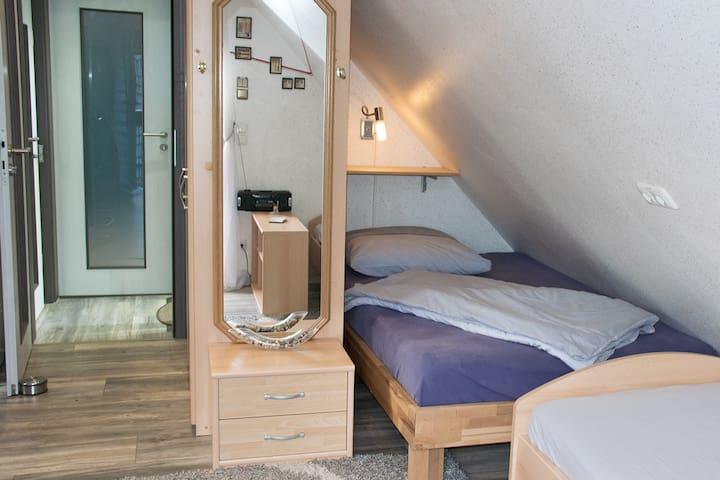 Einzelzimmer 1 mit zwei Einzelbetten. Gegenüber liegt das Einzelzimmer 2.