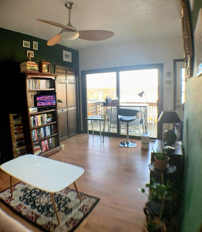 View of second living room with standing desk, view of upper balcony, and coffee table.