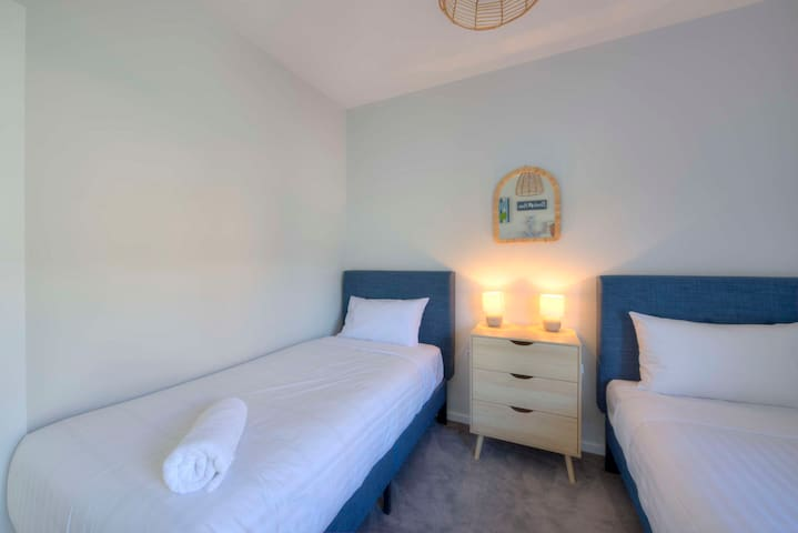 The second bedroom has two single beds.