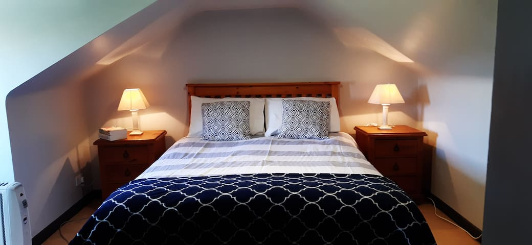 Upstairs  en suite bedroom with slooped ceiling.