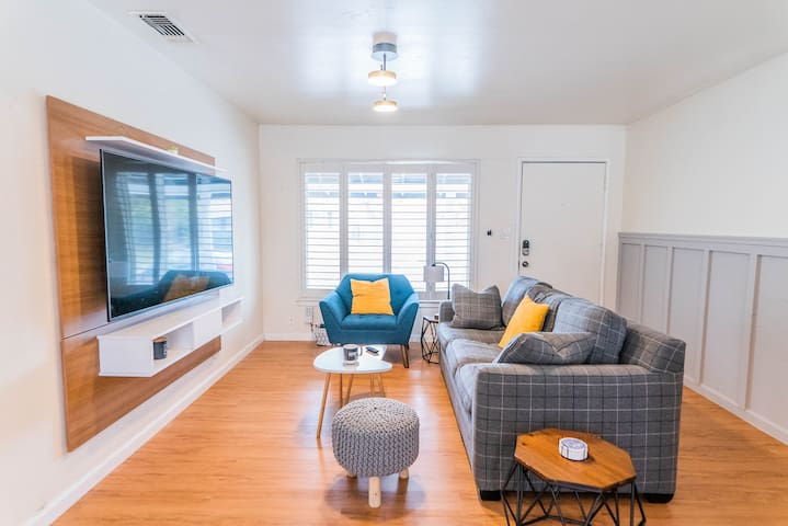 Lounge around in this modern, sleek living room featuring 7ft sofa bed, modern accent chair, nesting coffee tables, two end tablesand puff chair. 65in Roku SMART TV with free access to Netflix and HBO.