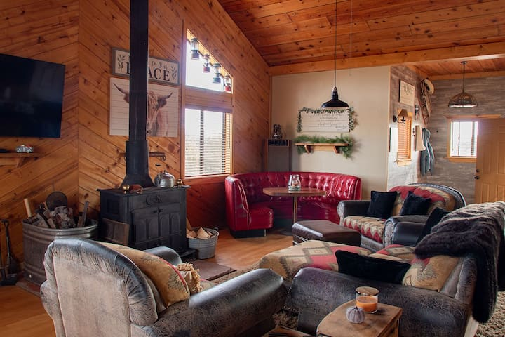Great room with 2 couches, oversized chair and wood stove along with a fun diner style table seating for 6.