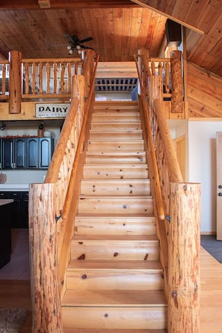 Stairs from the great room lead up to the open loft with queen bunks, twin bunks and 2 bean bag beds.