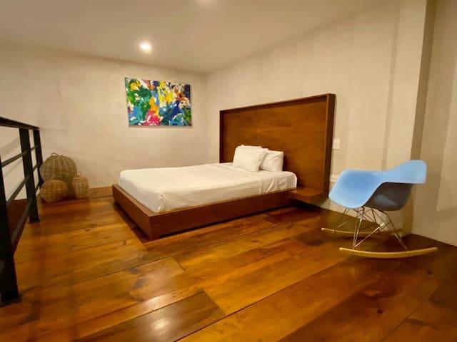 Open bedroom with comfortable queen size bed on the mezzanine overlooking the living room