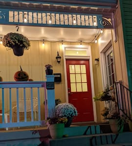 String lights on porch, well placed street lighting and a illuminated business sign light the entrance well.