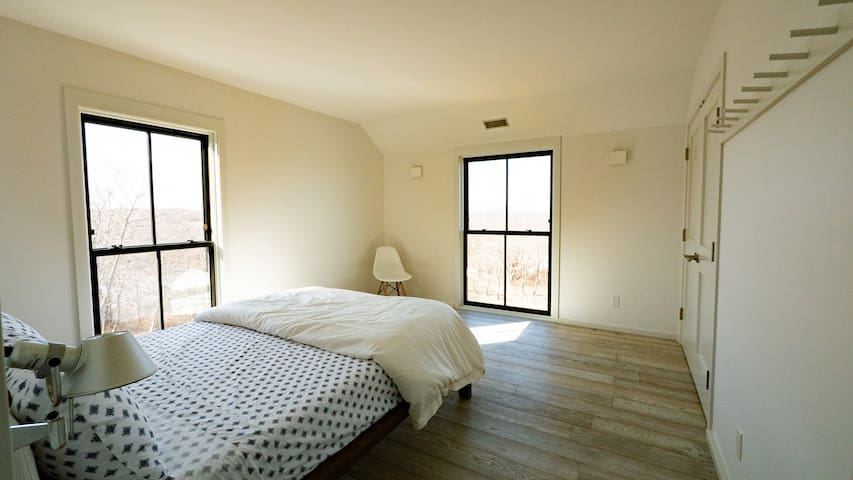The second bedroom has a queen size bed and west-facing and north-facing floor to ceiling windows.