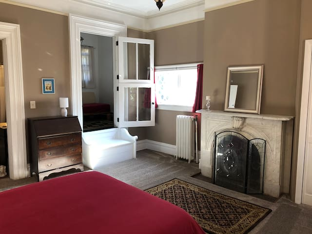 """Spacious bedroom with decorative marble fireplace, looking into """"half-bedroom."""""""