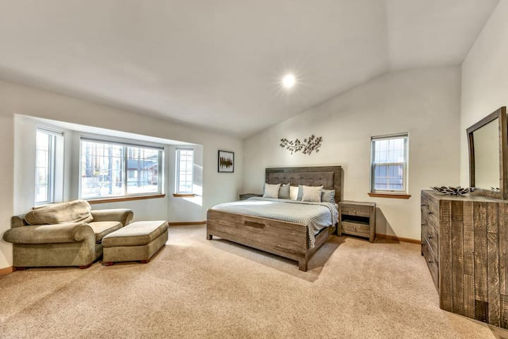 The upstairs master bedroom has a king bed, lounge chair, and plenty of natural light streaming in from the bay windows