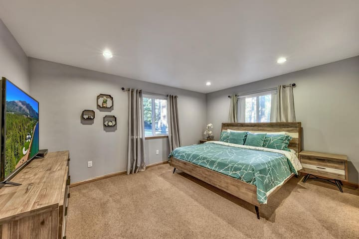 The downstairs master bedroom has a king bed, large TV, and ensuite bathroom