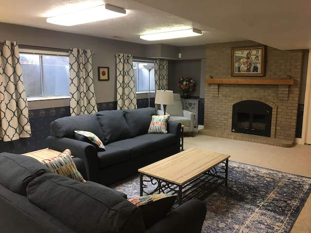 """Well lighted family room with sofa bed, fireplace and 65"""" smart TV"""