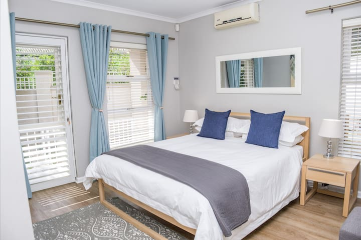 Sunny master bedroom (queen size bed) with aircon, door leading to outdoor patio
