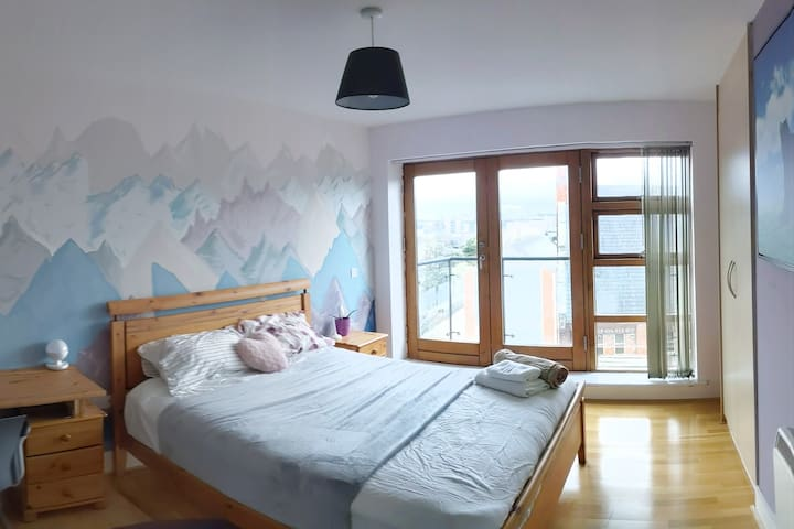 Master bedroom large built in press, opens up to a balcony and has its own bathroom. King size bed. Wall art.