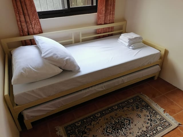Room C of the extension house. Has 1 single bed with a pull-out, a drawer, and an electric fan. Can accommodate 2 persons.