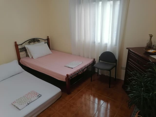 Room B of the extension house. Has 1 double bed, 1 family-size sofa bed, an electric fan, and drawers.  Can accommodate 2-4 persons.