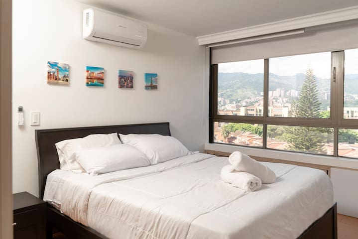 """Main Room Queen size bed with a beautiful City view very spacious and fresh. The apartment is located in the 5th floor, it has big windows is very fresh and AC. 55"""" TV."""