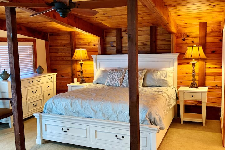 King bed in master bedroom with access to deck and lake view