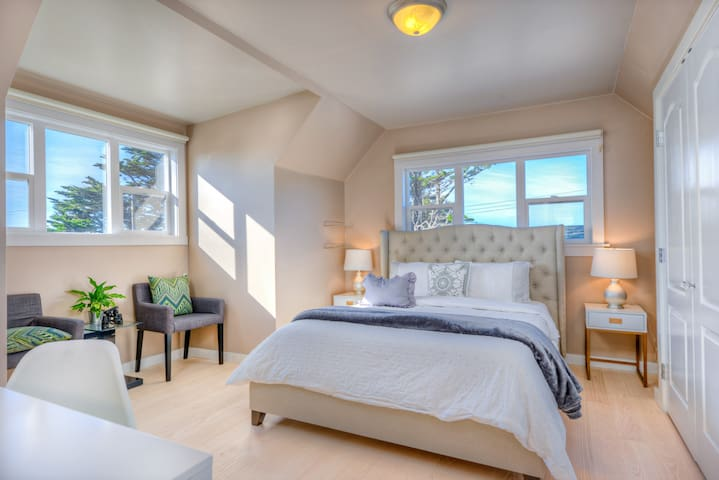 Primary bedroom with amazing ocean view, seating area, and computer desk.