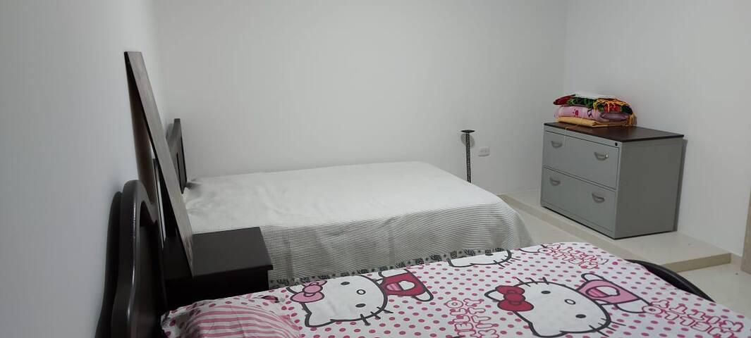 habitación principal, baño privado, cama doble + sencilla + organizador + mesa de noche.