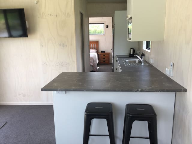 Kitchen has an island bench with breakfast bar with bar stools.  Kitchen has a water filter, microwave oven, 2 plate ceramic range hob and fridge freezer. Also a 40inch TV