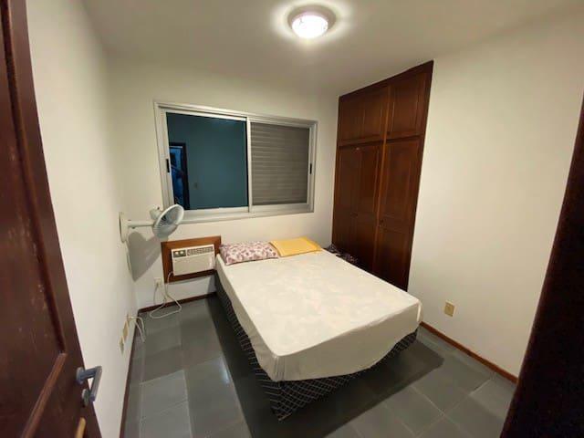 quarto com cama de casal, ar condicionado e ventilador