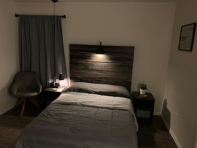 Comfortable Room with reading chair and bedside lamp. The room also has a ceiling fan, an additional portable fan, and heater for comfort!