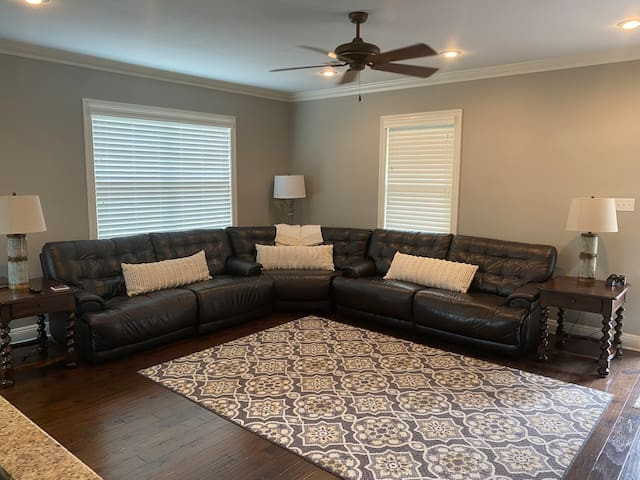 Large living room with oversized sectional couch with reclining features.