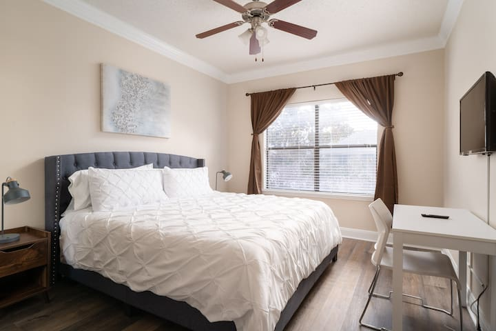 2nd King bedroom with memory foam mattress, duvet covers, cozy pillows and bed sheets, 32 inch smart TV, two wood end tables and lamps, dark-out curtains, and elegant desk and chair