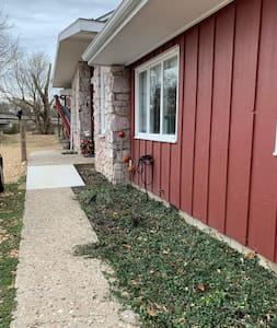The sidewalk from the asphalt driveway has a ramp on both sides for easy access to the patio but requires a small step up to the breezeway.