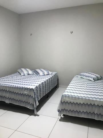Quarto com uma cama de casal e uma de solteiro