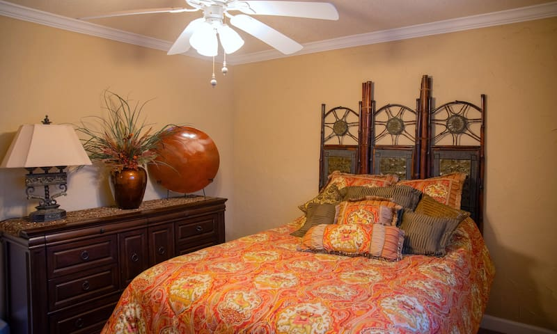 Queen sized Bed with soft linens & plush pillows for a great night sleep in the Guest room with closet, Ceiling fan for good airflow & dresser for longer stays.