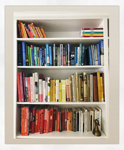 Color coded bookshelves in the study