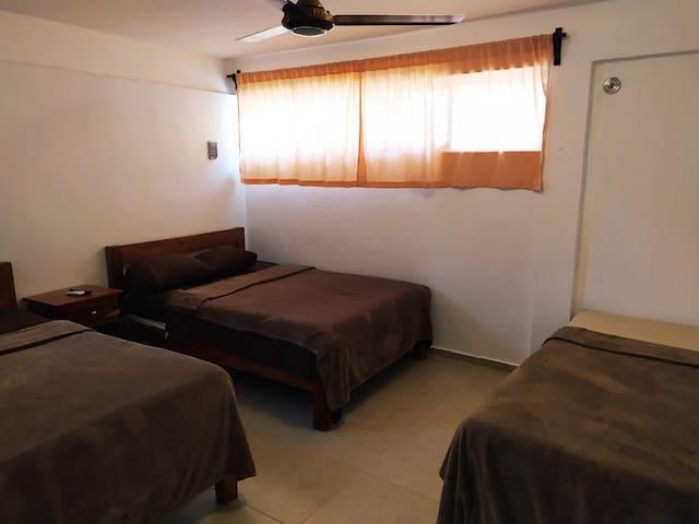 Cómoda habitación con dos camas, dos matrimoniales y una individual, Aire acondicionado y un ropero para acomodar la ropa, ademas de una TV con mas de 70 canales.