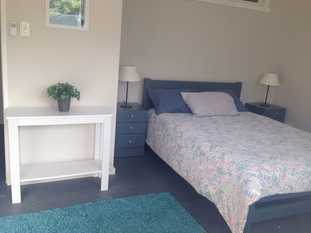 Dble bedroom w/ ceiling fan and large hanging cupboard w/ shelves. Private garden views.