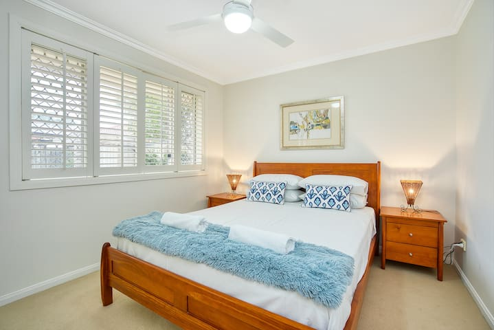 A secondary bedroom features a queen bed topped with hotel-quality linen and well as a wardrobe