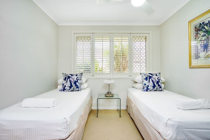 A third bedroom has streams of natural light coming in through the large window and features two single beds