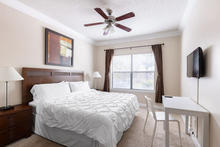 2nd King bedroom with memory foam mattress, duvet covers, cozy pillows and bed sheets, 32 inch smart TV, wood end tables and lamps, dark-out curtains, and elegant desk and chair.  This room has an attached bathroom.