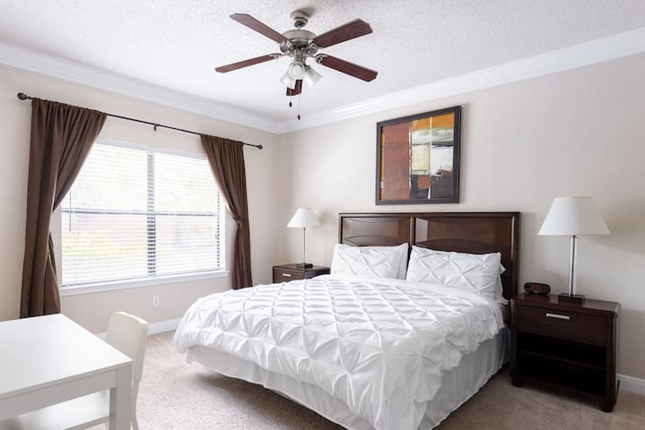 Master King bedroom with memory foam mattress, duvet covers, cozy pillows and bed sheets, 32 inch smart TV, wood end tables and lamps, dark-out curtains, and elegant desk and chair.  This room has an attached bathroom.