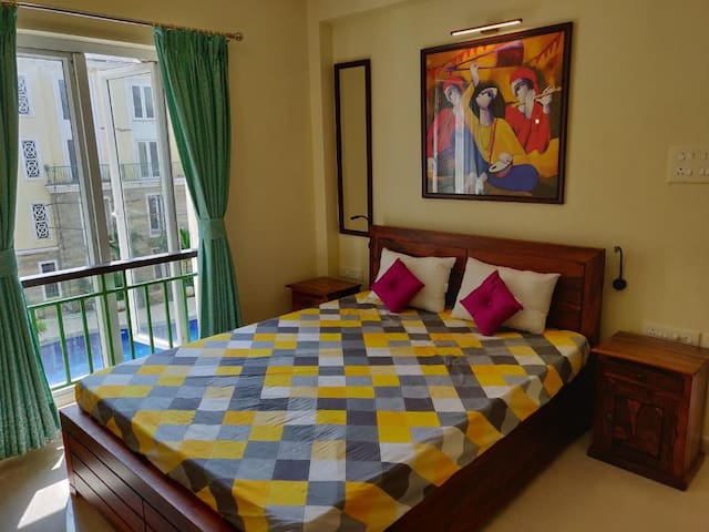 Guest Bedroom with a Double Bed, overlooking the pool. The room has an attached washroom