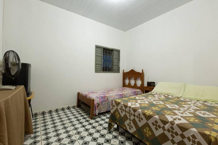 quarto 2 com cama de casal e de solteiro e janela para varanda do fundo