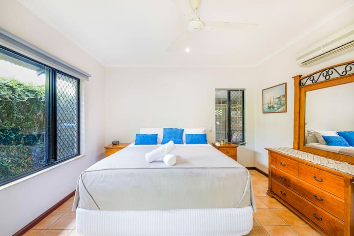 A master bedroom overlooks the pool and features a spacious king bed as well as an ensuite and a wooden vanity